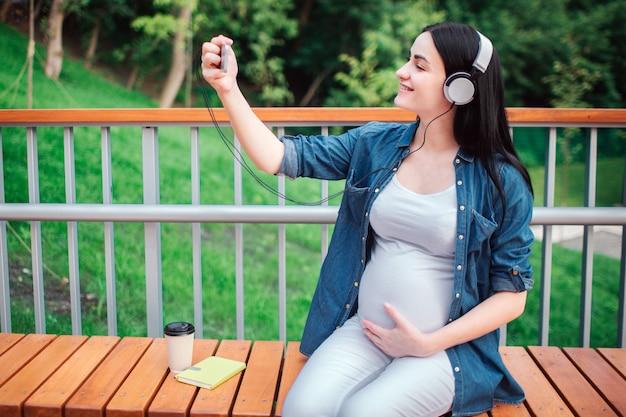 Retrato de un cabello negro feliz y orgullosa mujer embarazada en el parque. ella está sentada en un banco de la ciudad. la futura madre está escuchando música en el parque con un niño no nacido
