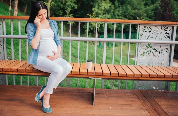 Retrato de un cabello negro feliz y orgullosa mujer embarazada en el parque. imagen de primer plano de modelo femenino tocando su vientre con las manos