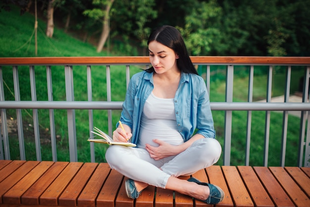 Retrato de un cabello negro feliz y orgullosa mujer embarazada en el parque. la modelo femenina está escribiendo notas en su cuaderno.