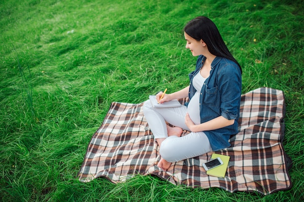 Retrato de un cabello negro feliz y orgullosa mujer embarazada en el parque. la modelo femenina está sentada en el césped y está escribiendo notas.