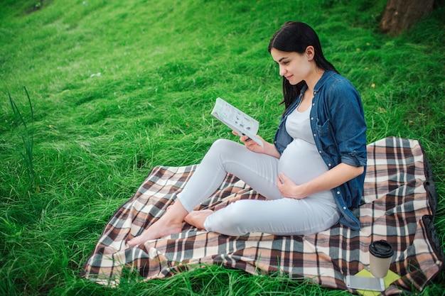 Retrato de un cabello negro feliz y orgullosa mujer embarazada en el parque. la modelo femenina está sentada en el césped y la modelo femenina está leyendo un libro