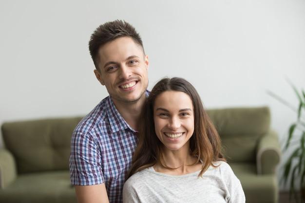 Retrato en la cabeza de una sonriente pareja milenaria atractiva mirando a la cámara