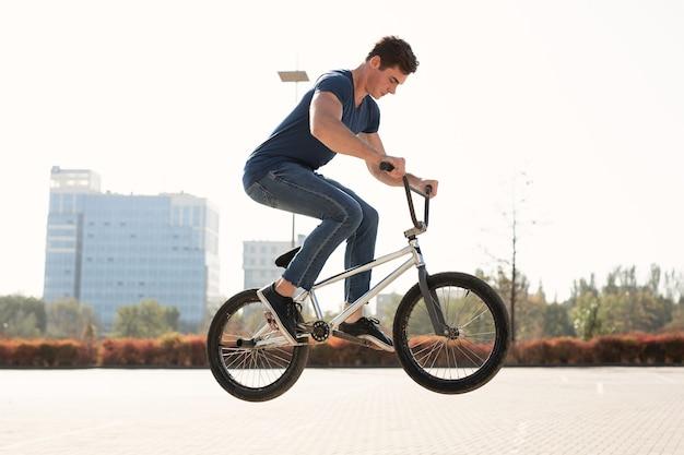 Retrato de la calle de un ciclista de bmx en un salto en la calle en el paisaje de la ciudad