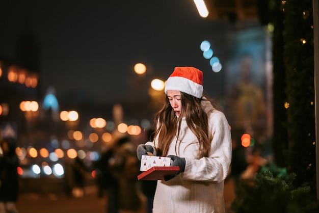 Retrato de calle de noche de joven bella mujer actuando emocionado. guirnalda de luces festivas.