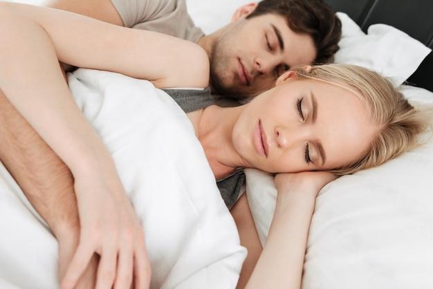 Retrato de calma guapo pareja durmiendo en la cama