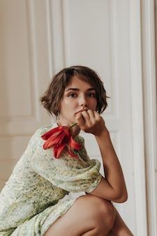 Retrato de calma joven morena mujer de pelo corto en vestido floral se inclina sobre las rodillas, mira al frente y sostiene flor roja
