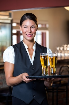 Retrato de camarera con bandeja de servir con dos vasos de cerveza