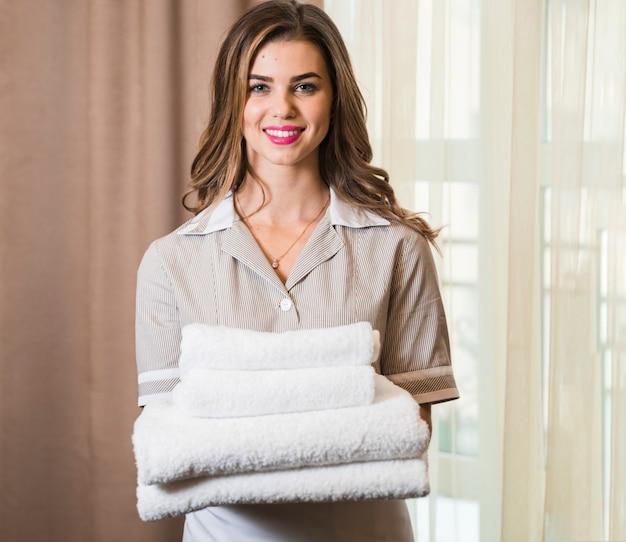 Retrato de una camarera de hotel sonriente en la sala con pila de toallas blancas