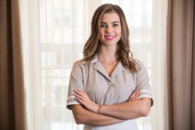Retrato de una camarera joven confiada sonriente en la habitación de hotel