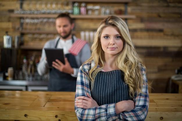 Retrato de camarera de pie con los brazos cruzados en el mostrador