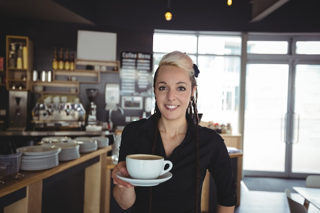 Retrato de camarera de pie con una taza de café
