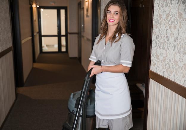 Retrato de una camarera sonriente de pie en el pasillo del hotel con aspiradora