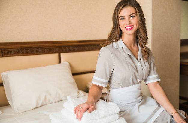 Retrato de una camarera sonriente sentada en la cama con una pila de suaves toallas dobladas