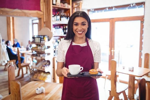 Retrato de camarera sosteniendo una taza de café y aperitivos
