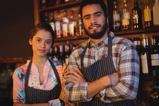 Retrato de camarero y camarera de pie con los brazos cruzados.