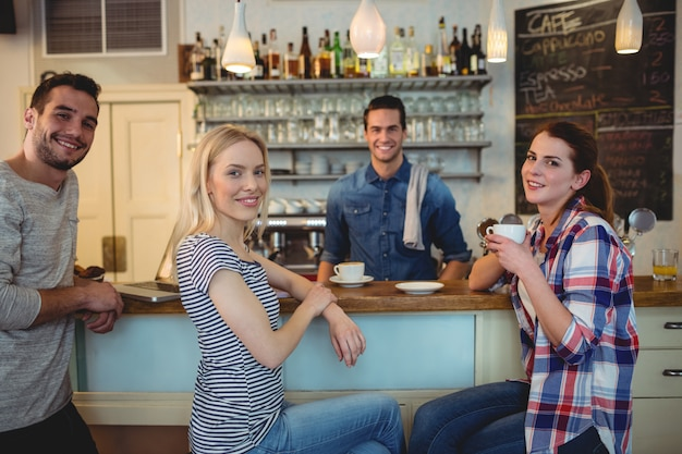 Retrato de camarero con clientes felices en el café