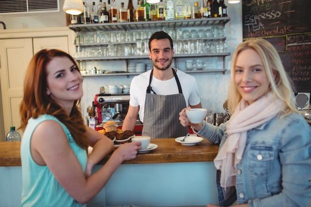 Retrato de camarero con clientes felices en la cafetería.