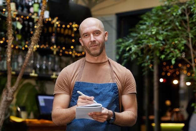 Retrato de camarero maduro en uniforme está listo para tomar el pedido que mira de pie en el restaurante