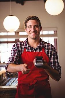 Retrato de camarero mostrando máquina de tarjeta de crédito