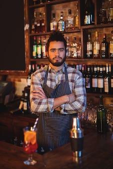 Retrato de camarero de pie con los brazos cruzados en el mostrador