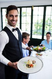 Retrato de camarero de pie con comida junto a los clientes
