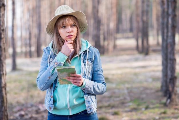 Retrato de un caminante femenino contemplado que sostiene el mapa en la mano que mira lejos