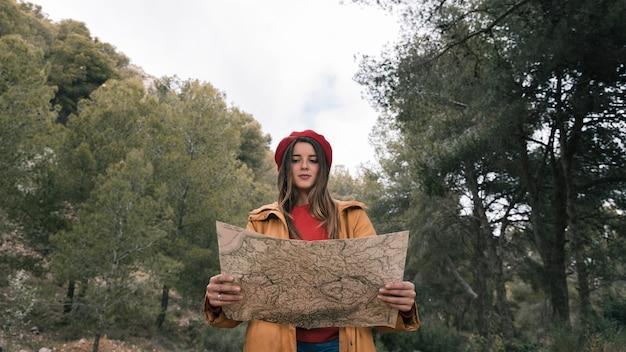 Retrato de un caminante femenino que se coloca en el bosque que lee el mapa