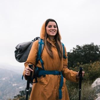 Retrato de un caminante femenino sonriente que sostiene el palillo que camina que mira la cámara