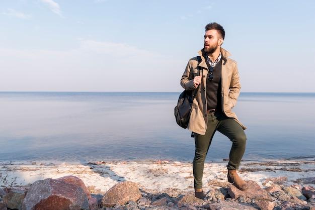 Retrato de un caminante masculino con el bolso en el hombro que se coloca delante del mar