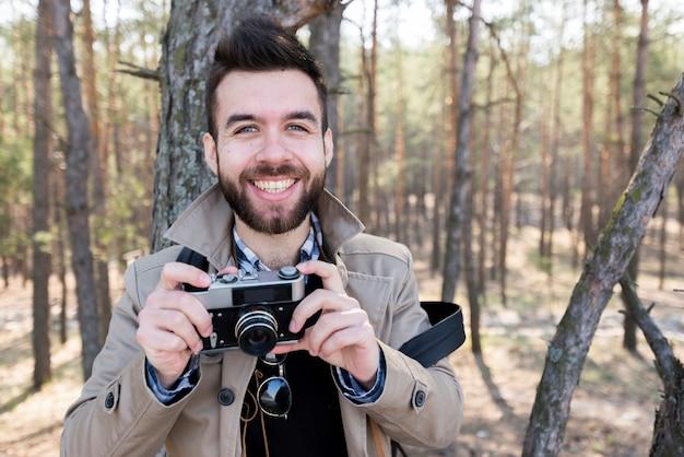 Retrato de un caminante masculino sonriente que sostiene la cámara en la mano que mira la cámara