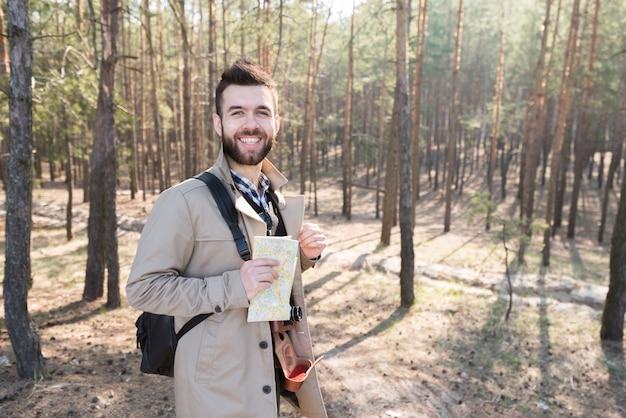 Retrato de un caminante masculino sonriente que sostiene un mapa genérico en el bosque