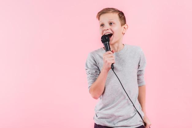 Retrato de una canción confiada del canto del muchacho en el micrófono contra fondo rosado