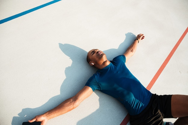 Retrato de un cansado joven africano fitness hombre en auriculares