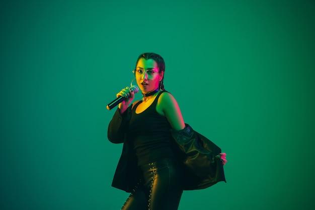 Retrato de la cantante caucásica aislado en la pared verde en luz de neón. modelo de mujer hermosa en ropa negra con micrófono. concepto de emociones humanas, expresión facial, publicidad, música, arte.
