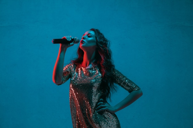 Retrato de cantante femenina aislado en la pared azul del estudio en luz de neón