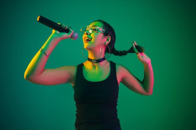 Retrato de cantante femenina aislado en la pared verde del estudio en luz de neón
