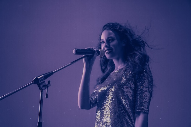 Retrato de cantante femenina caucásica aislado en estudio púrpura en luz de neón