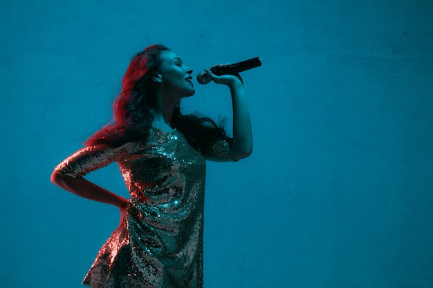 Retrato de cantante de raza caucásica aislado sobre fondo azul de estudio en luz de neón. modelo de mujer hermosa en vestido brillante con micrófono. concepto de emociones humanas, expresión facial, publicidad, música, arte.