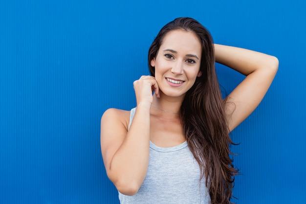 Retrato de la cara de una hermosa joven sonriente con azul