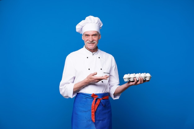 Retrato del carismático chef barbudo sosteniendo una canasta con huevos frescos mientras posa contra la pared azul