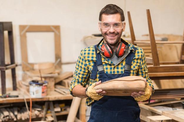 Retrato de carpintero hombre sonriente sosteniendo modelo de madera incompleta