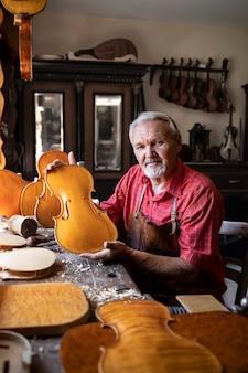 Retrato de carpintero senior en su antiguo taller haciendo violines instrumento musical para la academia de artes