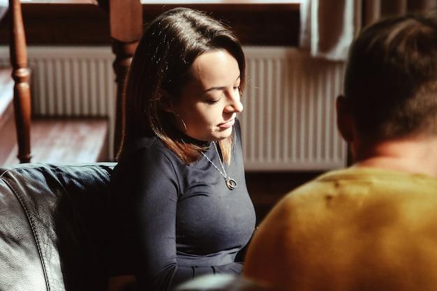 Retrato casual de mujer joven en reunión de negocios en casa de campo en la sala de estar del pasillo. la mujer lidera la discusión con socios comerciales, ofreciendo ideas y escuchando la opinión de sus colegas.
