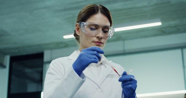 Retrato de la caucásica hermosa trabajadora de laboratorio haciendo un análisis de sangre en el tubo de vidrio en las manos. de cerca.