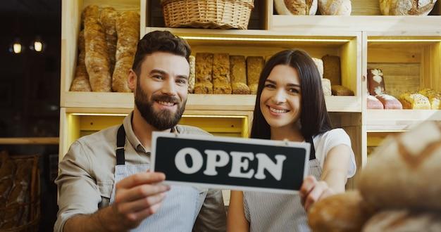 El retrato del caucásico masculino y femenino sonrió panaderos sosteniendo juntos un letrero abierto y posando con él dentro de la tienda.