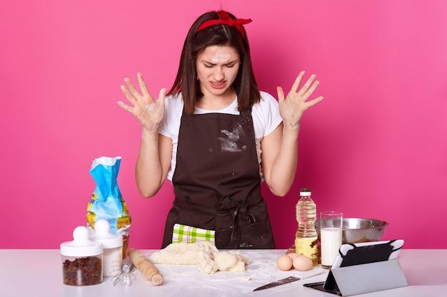 El retrato de cerca de ama de casa cansada o panadero se ve triste, pasa muchas horas preparando el pastel de pascua, no puede hacer la masa con la consistencia deseada, quiere dejar de hornear, aislado en rosa.