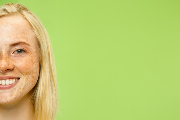 Retrato de cerca de la mujer joven caucásica en la pared verde. modelo de mujer en camisa amarilla con cabello rubio y pecas. concepto de emociones humanas, expresión facial.