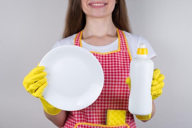 Retrato de cerca recortada de buenos deberes satisfechos disfrutando del resultado niña sosteniendo mostrando plato limpio y jabón líquido que usó pared gris aislada