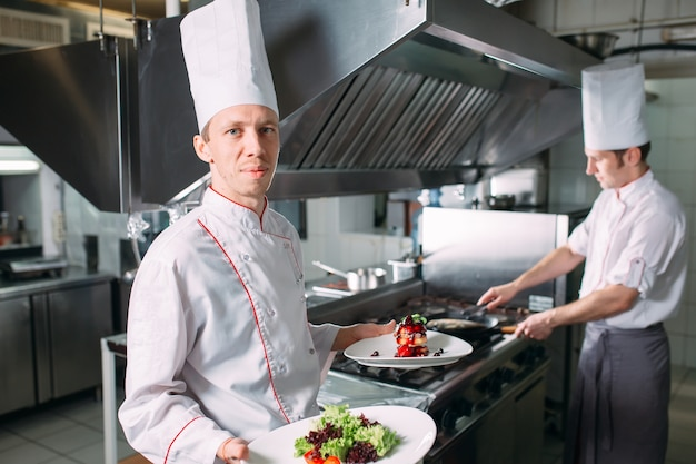 Retrato del chef en la cocina del restaurante con un plato de foie gras.