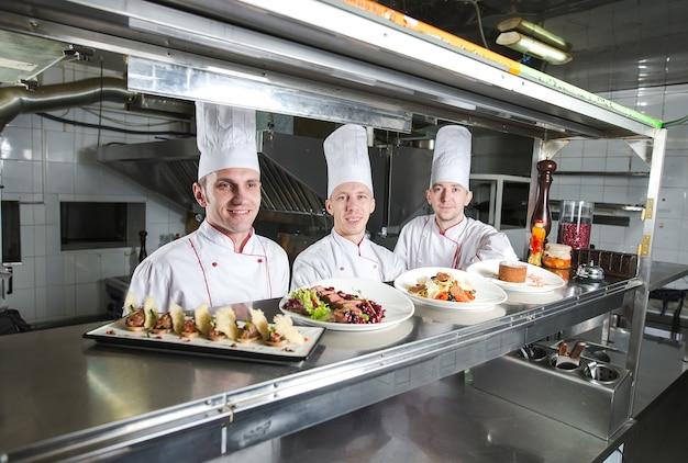 Retrato de un chef con comida cocinada en la cocina en el restaurante.